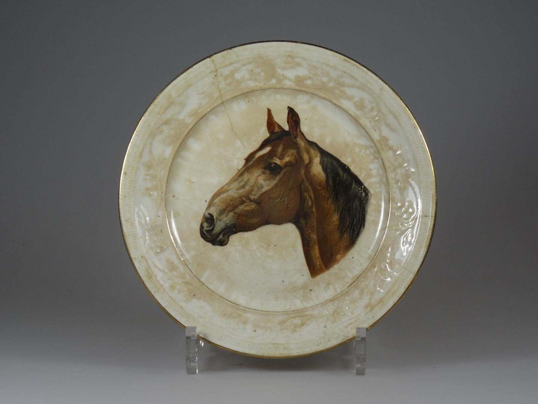 Bord waarop paardenhoofd met reliëfrand