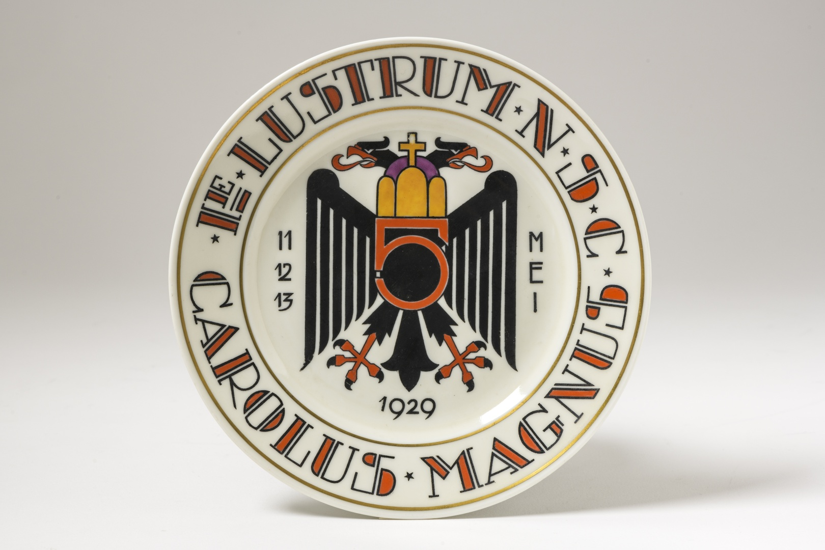 Wandbord: tweekoppige adelaar met aan beide zijden 11 12 13 MEI waaronder 1929