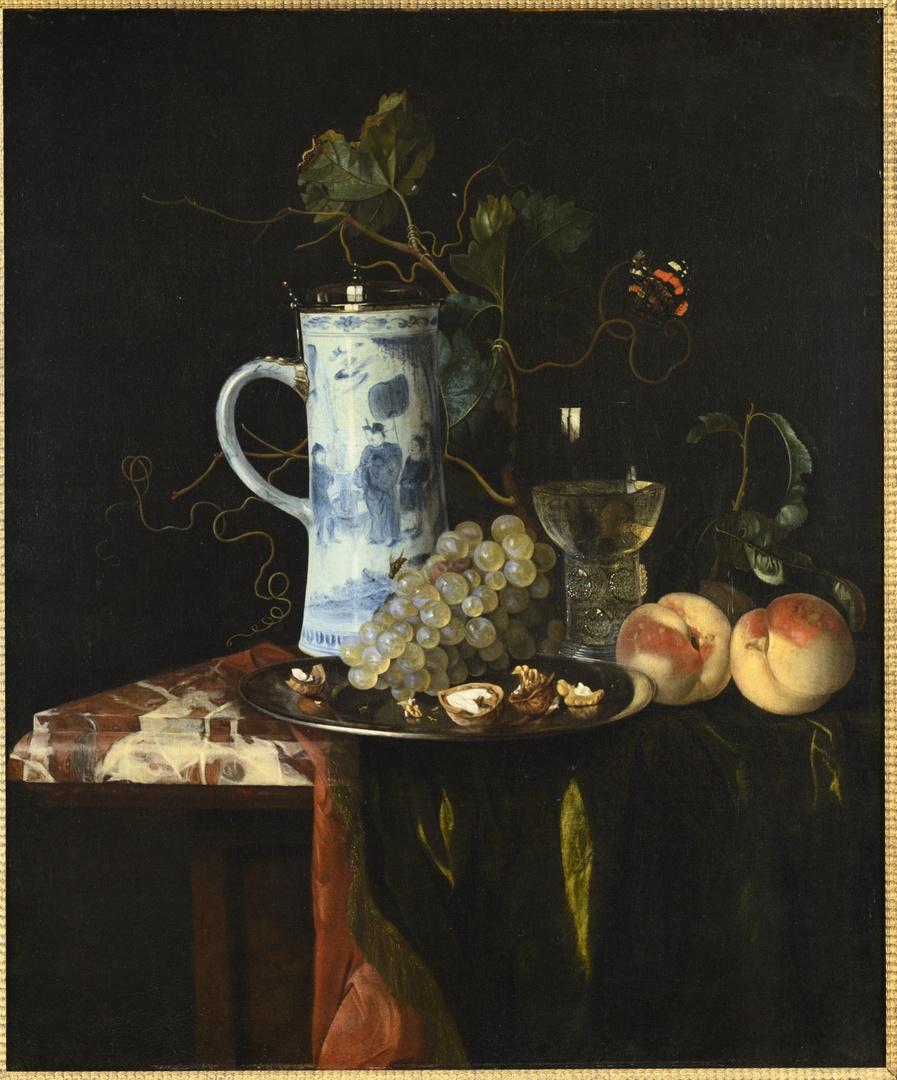 Stilleven met een kan van chinees porselein, druiven, walnoten, roemer, perziken en een kleed op een marmeren tafel